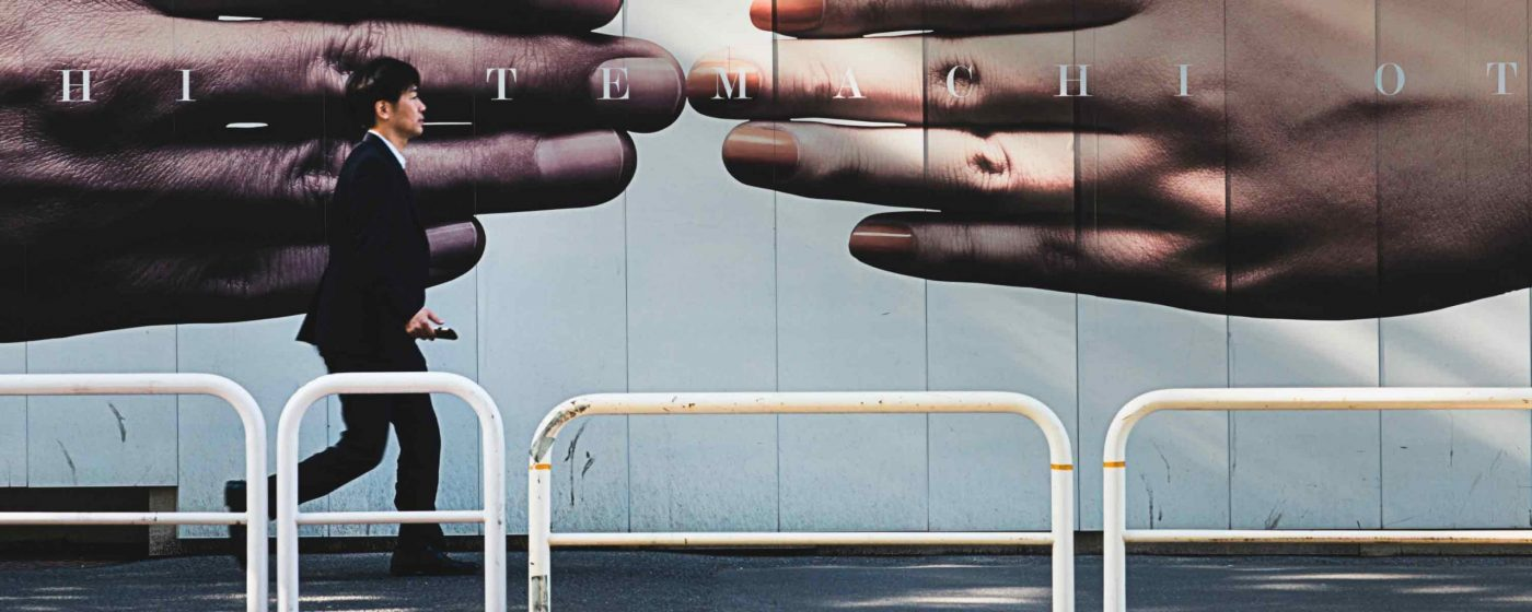 Text oder Werbetext auf Plakatwand im Hintergrund – asiatischer Mann im Vordergrund