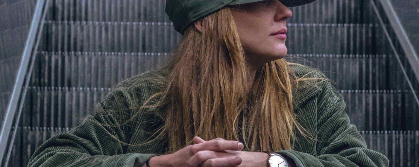 Frau auf Rolltreppe, Frau mit modischer Mütze