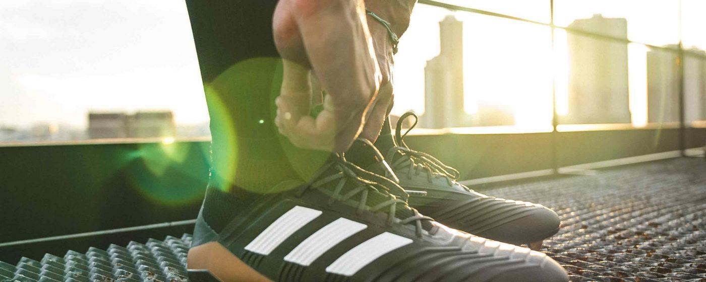 Sportler bindet sich die Schuhe zu, auf Brücke in Großstadt