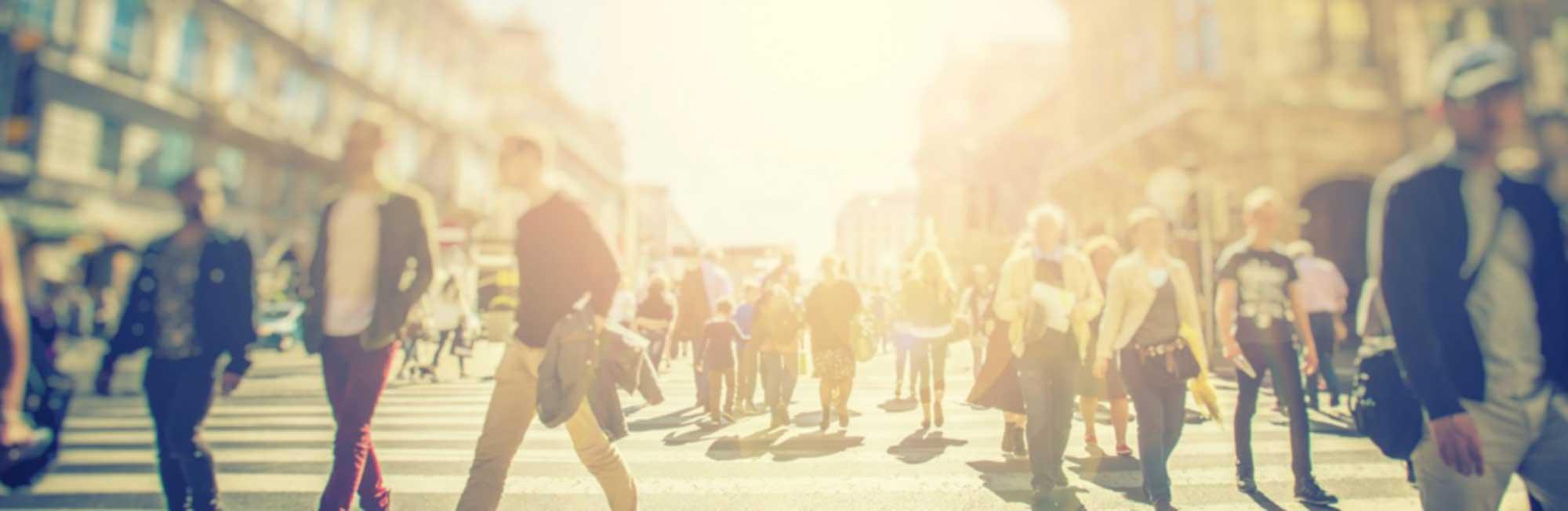 Menschen flanieren durch Sonnenlicht